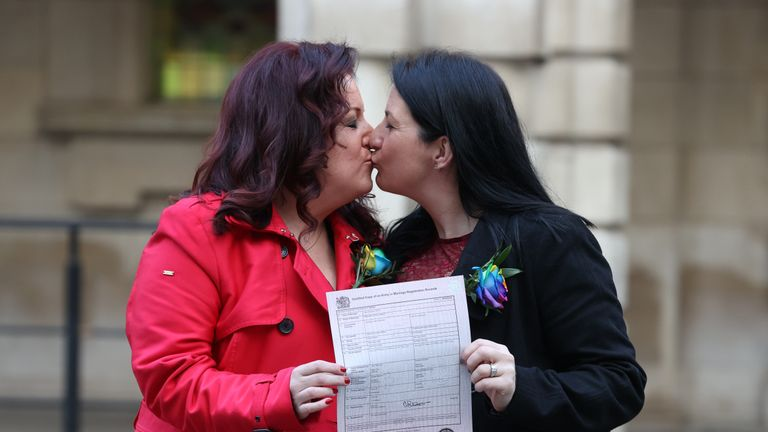 IMAGE PIXELATED BY PA PICTURE DESK Amanda McGurk (left) and Cara McCann outside Belfast City Hall after becoming the first couple in Belfast to convert their civil partnership into a marriage. From today same-sex couples across Northern Ireland are able to marry through the official conversion of existing civil partnerships following a change in the law.