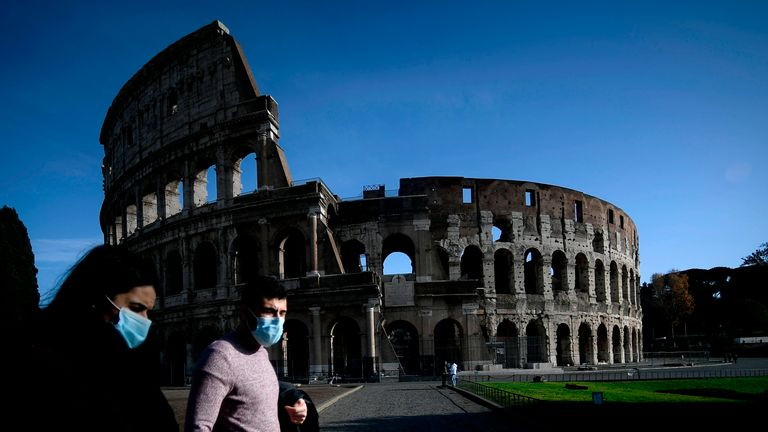 A face masked couple walks by the ancient Colosseum in downtown Rome on December 5, 2020, during the government's restriction measures to curb the spread of the COVID-19 pandemic caused by the novel coronavirus. - The Italian government imposed tighter restrictions to Italian regions on December 4 as it tries to stem escalating new cases of coronavirus during the Christmas holidays. (Photo by Filippo MONTEFORTE / AFP) (Photo by FILIPPO MONTEFORTE/AFP via Getty Images)