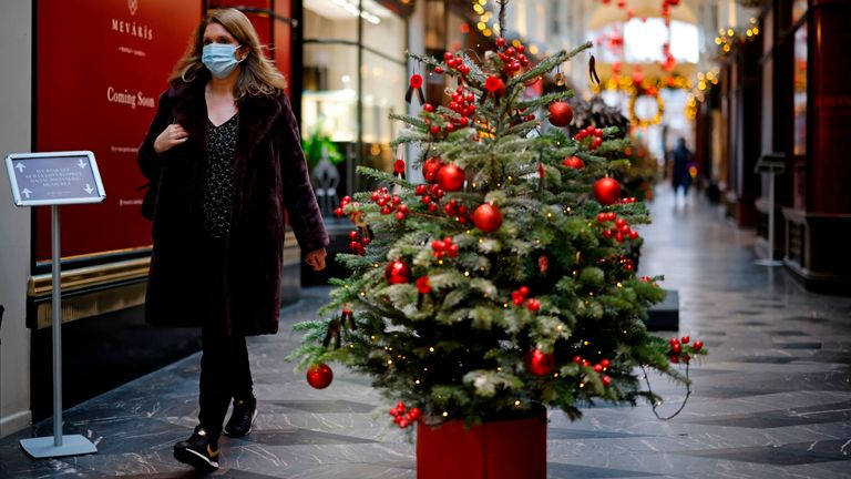 "A pedestrian wearing a protective face covering to combat the spread of the coronavirus, walks past Christmas-themed window displays inside Burlington Arcade in central London on November 27, 2020, as life under a second lockdown continues in England. - England will return to a regional tiered system when the national stay-at-home order ends on December 2, and 23.3 million residents in the worst-hit areas are set to enter the ""very high"" alert level. (Photo by Tolga Akmen / AFP) (Photo by TOLGA AKMEN/AFP via Getty Images)"