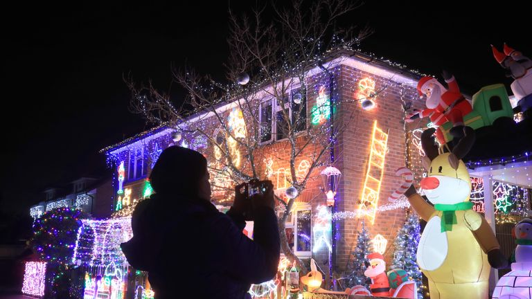 A member of the public takes a photograph of the Christmas light display on a house in Saxifrage Way, Worthing.