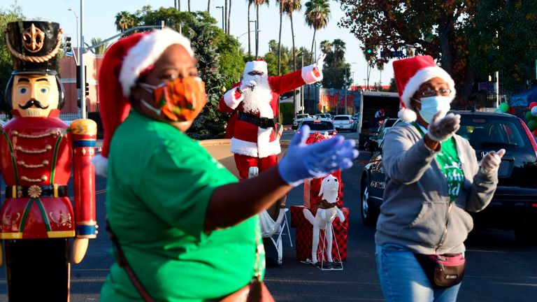 Volunteers in face masks and Santa hats direct arriving vehicles as Santa Claus entertains his audience at the toy and food giveaway at the Crenshaw YMCA Holiday Spectacular in Los Angeles, California on December 13, 2020. (Photo by Frederic J. BROWN / AFP) (Photo by FREDERIC J. BROWN/AFP via Getty Images)