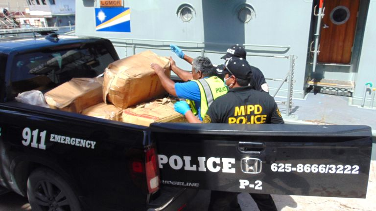 """A photo on December 15, 2020 shows Marshall Islands police loading a box filled with one-kilo """"bricks"""" of cocaine into a police pickup truck from a patrol vessel that transported the cocaine from a remote outer atoll to Majuro for confiscation and destruction. - An 18-foot fiberglass boat was found washed up on Ailuk Atoll, a remote atoll with about 400 people, in the Marshall Islands last week with 649 kilos (1,340 pounds) of cocaine sealed in its hold under the deck. (Photo by Giff JOHNSON / AFP) (Photo by GIFF JOHNSON/AFP via Getty Images)"""