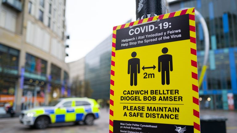 CARDIFF, WALES - DECEMBER 17: A yellow COVID-19 warning sign near a police car on the Hayes on December 17, 2020, in Cardiff, Wales. A two-household limit will be in place from December 23 to December 27 and three in the rest of the UK. In Wales, non-essential shops will close at the end of trading on Christmas Eve with an alert level four lockdown starting four days later. Close-contact services, such as hair salons also have to shut before Christmas, and all pubs, cafes and restaurants will close at 18:00 GMT on Christmas Day. (Photo by Matthew Horwood/Getty Images).