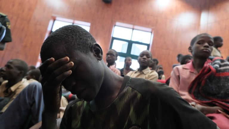 A distressed child covers his face while gathering at the Government House with other students from the Government Science Secondary school, in Kankara, in northwestern Katsina State, Nigeria upon their release on December 18, 2020. - More than 300 Nigerian schoolboys were released on Thursday after being abducted in an attack claimed by Boko Haram, officials said, although it was unclear if any more remained with their captors (Photo by Kola SULAIMON / AFP) (Photo by KOLA SULAIMON/AFP via Getty Images)