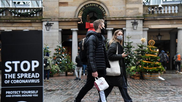 People walk past a sign advising social distancing in Covent Garden in London.