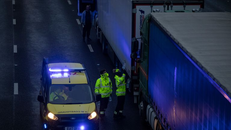 SELLINDGE, ENGLAND - DECEMBER 21: The coastguard give out bottles of water as lorries queue on the M20 on December 21, 2020 in Sellindge, England. Citing concern over a new covid-19 variant and England's surge in cases, France temporarily closed its border with the UK late Sunday, halting freight and ferry departures from the port of Dover for 48 hours. France also joined several other European countries in stopping rail and air travel from the UK. (Photo by Dan Kitwood/Getty Images)
