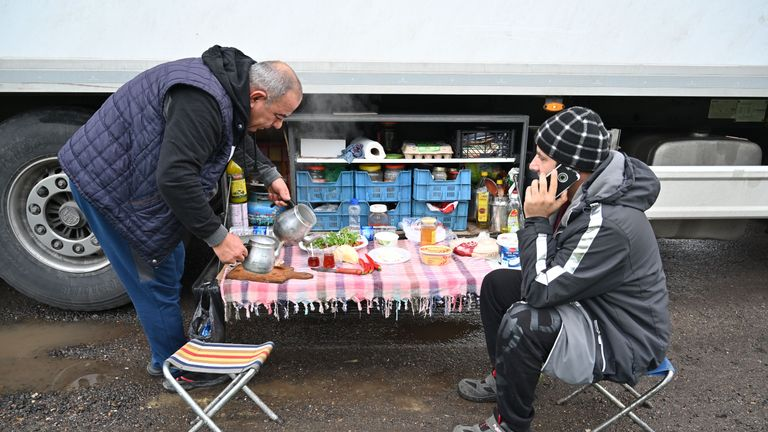 Turkish long-haul truck drivers sit down to breakfast at a truck stop off the M20 motorway which leads to the Port of Dover, near Ashford in Kent, south east England on December 22, 2020, as they queue unable to continue their journeys after France closed its borders to accompanied freight arriving from the UK due to the rapid spread of a more-infectious new coronavirus strain. - Britain sought to sound a note of calm saying they were working as fast as possible to unblock trade across the Channel after France shut its borders to UK hauliers in a bid to contain a new variant of the coronavirus. (Photo by JUSTIN TALLIS / AFP) (Photo by JUSTIN TALLIS/AFP via Getty Images)
