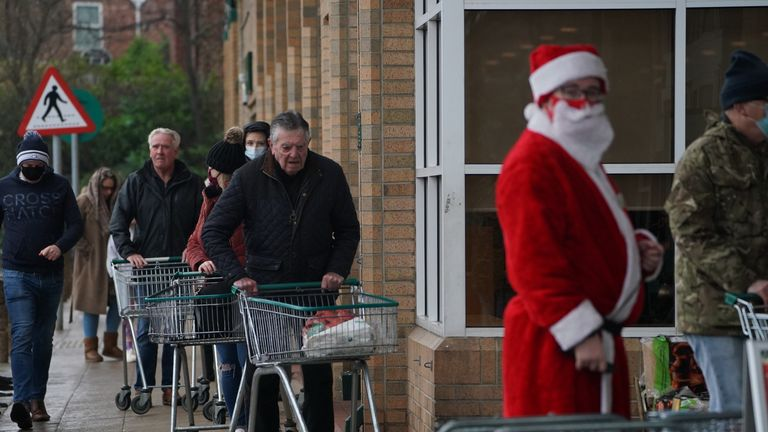 People queue outside a Morrisons supermarket in Whitley Bay, Tyne and Wear. Prime Minister Boris Johnson cancelled Christmas for almost 18 million people across London and eastern and south-east England following warnings from scientists of the rapid spread of the new variant of coronavirus.