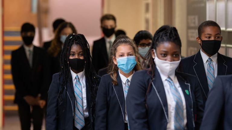 Year eight pupils wear face masks as a precaution against the transmission of the novel coronavirus as they walk along a corridor of Moor End Academy in Huddersfield, northern England on September 11, 2020. - Millions of children across England have returned to school after the Covid-19 lockdown with many schools introducing measures to enable as safe an environment as possible. (Photo by OLI SCARFF / AFP) (Photo by OLI SCARFF/AFP via Getty Images)