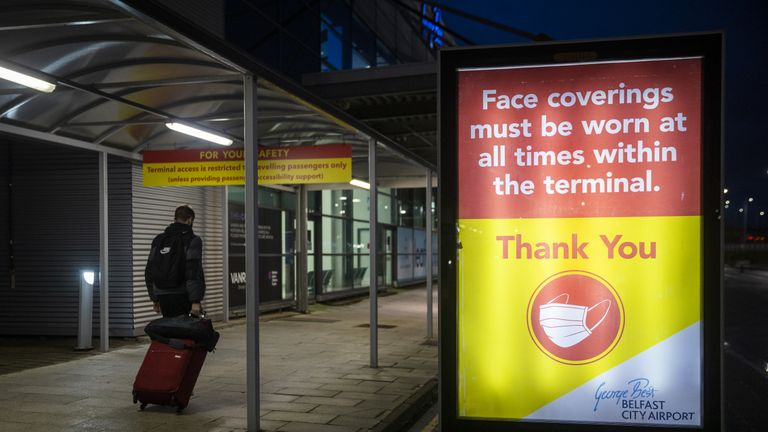 A man pulling luggage walks passed a sign that face coverings must be worn at all times within the terminal at George Best Belfast City Airport. Northern Ireland is considering strengthening its travel locator paperwork and is consulting legal experts after a mutation of coronavirus was discovered in London and Kent.