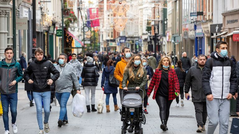 Pedestrians, some wearing face masks or coverings due to the COVID-19 pandemic, walk along a busy shopping street in Dublin on December 1, 2020, as Ireland exits a second partial coronavirus lockdown. - Ireland ended a second partial coronavirus lockdown on Tuesday, with non-essential shops, hairdressers and gyms unlocking their doors after six weeks of tough restrictions. Museums, galleries, libraries, cinemas and places of worship also reopened as the nation lifted virus curbs in place since October 22. On Friday, pubs and restaurants serving food will follow suit, although drinking-only establishments will remain shuttered. (Photo by PAUL FAITH / AFP) (Photo by PAUL FAITH/AFP via Getty Images)