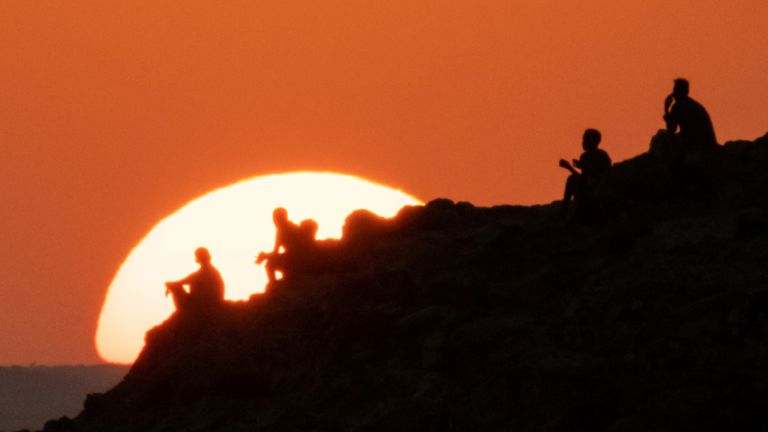 Ethiopian refugees who fled the Ethiopia's Tigray conflict watch the sunset on a hill at the Um Raquba refugee camp in Sudan's eastern Gedaref state on December 12, 2020. (Photo by Yasuyoshi CHIBA / AFP) (Photo by YASUYOSHI CHIBA/AFP via Getty Images)