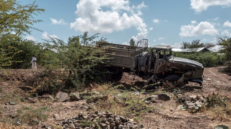 A damaged truck belonging to the Ethiopian Defense Forces lays behind a grave in the village of Bisober, in Ethiopia's Tigray region on December 9, 2020. - The November 14 killings represent just one incident of civilian suffering in Bisober, a farming village home to roughly 2,000 people in southern Tigray. In retrospect, Bisober residents say, the first sign of the conflict came seven months ago, when members of the Tigray Special Forces took over the village elementary school, which had been emptied because of the coronavirus pandemic. (Photo by EDUARDO SOTERAS / AFP) (Photo by EDUARDO SOTERAS/AFP via Getty Images)