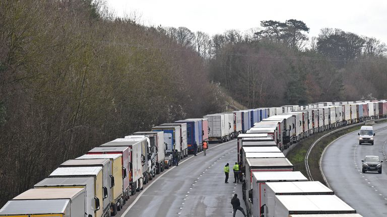 Freight lorries remain queued up on the M20 motorway, southbound, leading to the Port of Dover at Mersham in south east England on December 24, 2020, as rail and sea links between the UK and France are to remain open over Christmas to clear the backlog of thousands of trucks stranded by a new strain of coronavirus. - Thousands of European truckers on Wednesday spent a fourth night sleeping in the cabs of their vehicles, which are stuck close to the major cross-Channel port of Dover while the drivers wait to pass a Covid test, as required by France for travel. (Photo by JUSTIN TALLIS / AFP) (Photo by JUSTIN TALLIS/AFP via Getty Images)