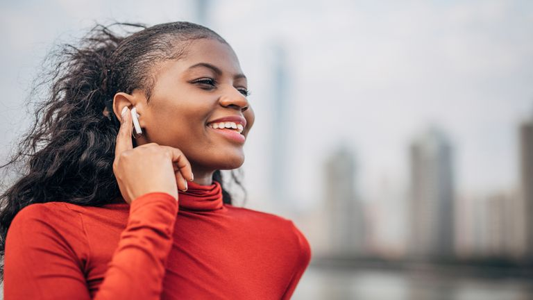 A woman standing in the city center by the river listening to music on Airpod wireless headphones.
