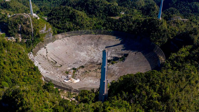 This aerial view shows damage to the Arecibo observatory after one of the main cables carrying the receiver broke in Arecibo, Puerto Rico, on December 1, 2020. - The radio telescope in Puerto Rico, which starred in the James Bond movie, collapsed.  Tuesday when the 900-ton receiving platform fell 450 feet (140 meters) and crashed onto the radio dish below.  (Photo by Ricardo Arduingo / AFP) (Photo by Ricardo Arduingo / AFP via Getty Images)