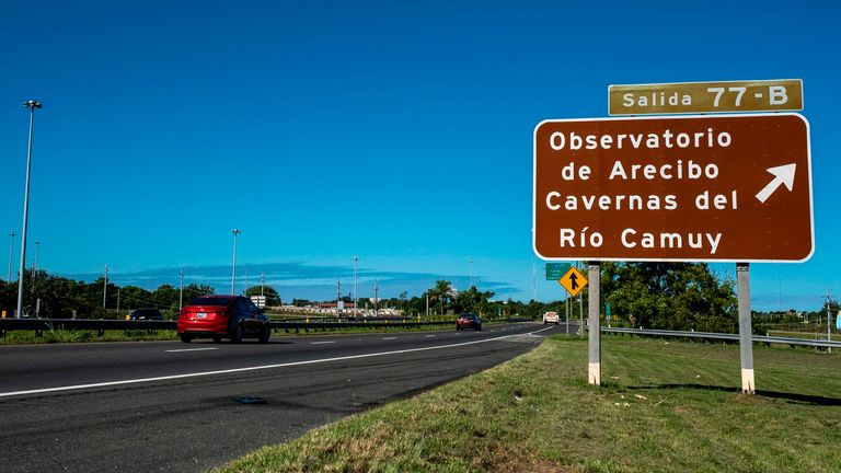 An indicative road sign towards the Arecibo Observatory is seen on the highway in Arecibo, Puerto Rico on December 1, 2020. - The Arecibo Observatory telescope in Puerto Rico, which once starred in a James Bond film, collapsed on December 1, 2020 when its 900-ton receiver platform fell 450 feet (140 meters) and smashed onto the radio dish below. Engineers had recently warned of the huge structure's decrepit condition, and the US National Science Foundation (NSF) announced only last month that it