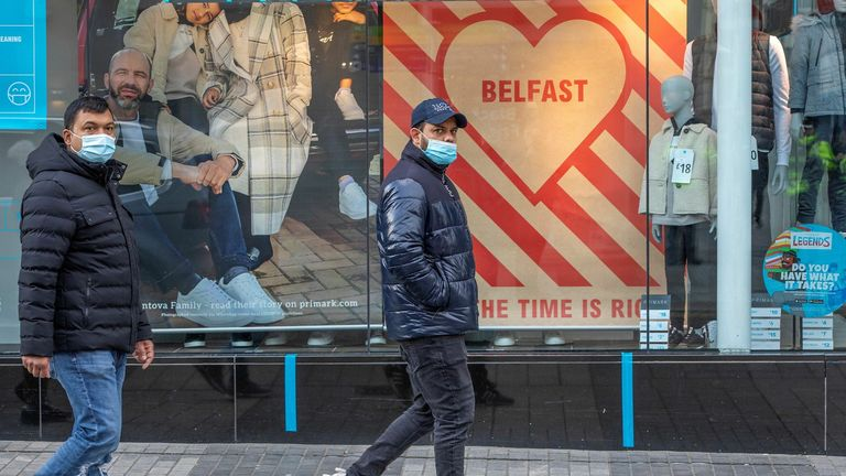 Pedestrians wearing a face mask or covering due to the COVID-19 pandemic, walks past a clothes shop in Belfast on November 27, 2020