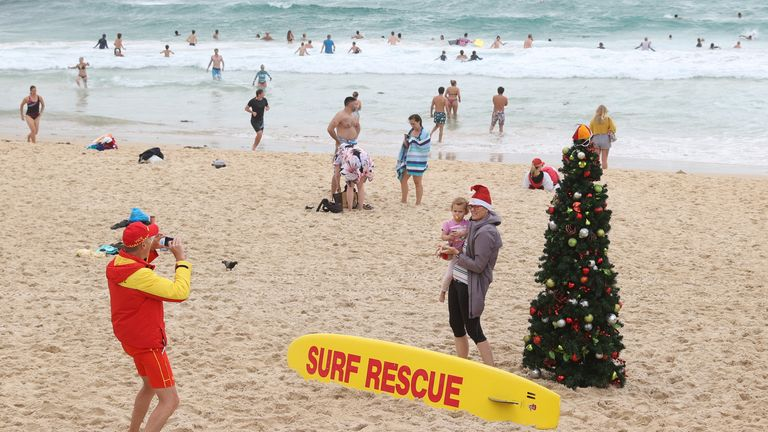 A person in a Santa hat poses for a photo with a child by a Christmas tree on Christmas Day at Bondi Beach in Sydney, Australia, December 25, 2020. REUTERS/Loren Elliott