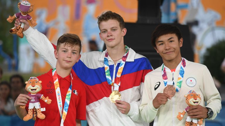 France's b-boy silver medal Martin (L), Russia's b-boy gold medal Bumblebee (C) and Japan's b-boy bronze medal Shigelix (R) pose in the podium at the Youth Olympic Games in Buenos Aires, Argentina on October 08, 2018.