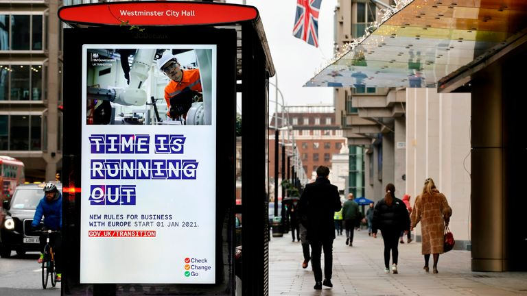 Pedestrians walk past an BTier 2 Coronavirus information displayed on an electronic advertising board at a bus stop in central London on December 14, 2020. - Britain's Prime Minister Boris Johnson and EU chief Ursula von der Leyen agreed Sunday to push on with post-Brexit trade talks despite the passing of a self-imposed deadline. Britain left the EU on January 31, 2020 after five decades of integration but a standstill transition period, under which it remains bound by the bloc's rules pending
