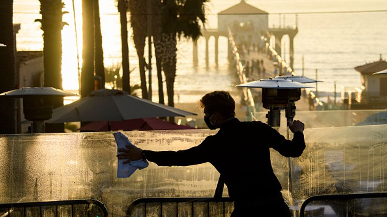An employee cleans a table divider at Manhattan Beach in LA