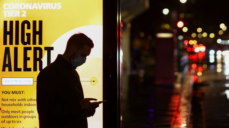 A man wearing a protective mask uses a phone at a bus stop, amidst the spread of the coronavirus disease (COVID-19), in London, Britain December 3, 2020. REUTERS/Henry Nicholls