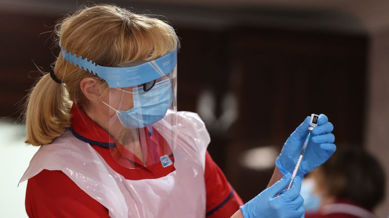 A Belfast nurse prepares to hand out vaccine to care home staff