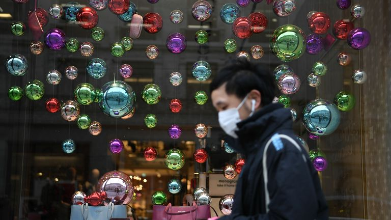 A man is seen walking past a festive window display in London during the pandemic