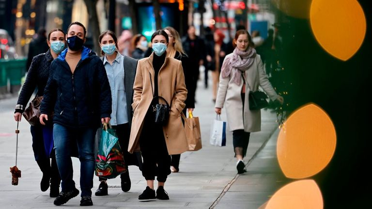 Pedestrians wearing a face mask or covering due to the COVID-19 pandemic, walk along Oxford Street in central London on December 22, 2020. - UK government borrowing continued to soar in November on emergency action to support the virus-hit economy which nevertheless rebounded stronger than expected in the third quarter, official data showed Tuesday.