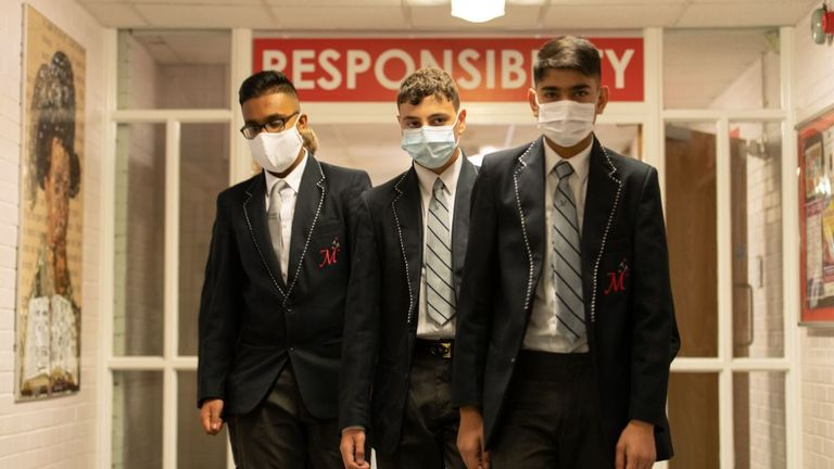 Year 10 pupils wear face masks as a precaution against the transmission of the novel coronavirus as they walk in a corridor at Moor End Academy in Huddersfield, northern England on September 11, 2020. - Millions of children across England have returned to school after the Covid-19 lockdown with many schools introducing measures to enable as safe an environment as possible. (Photo by OLI SCARFF / AFP) (Photo by OLI SCARFF/AFP via Getty Images)