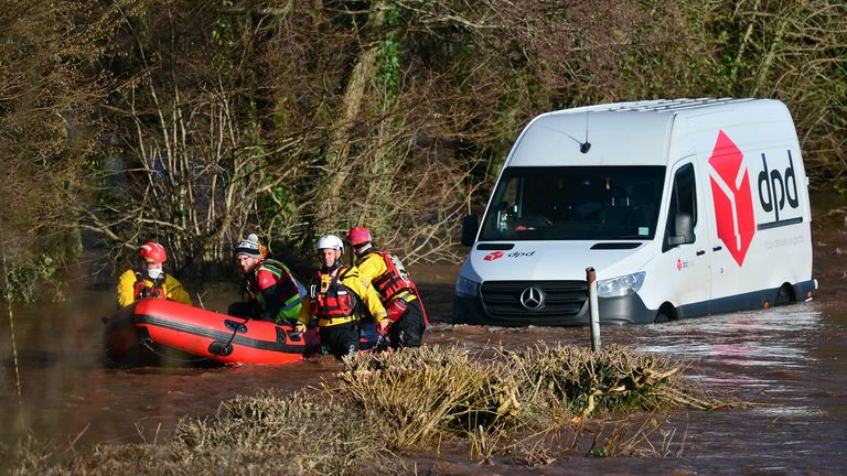 Emergency services rescue a DPD delivery van driver stranded in flood water in Newbridge on Usk, in Wales