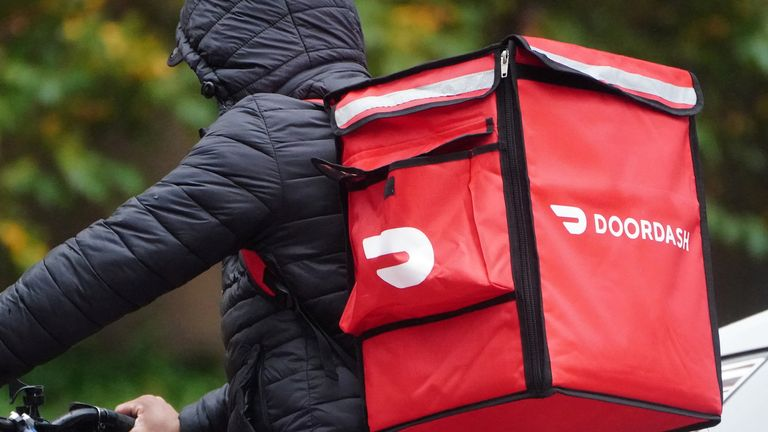 A delivery person for Doordash rides his bike in the rain in the Manhattan borough of New York City, New York, U.S., November 13, 2020