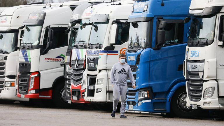 A driver wearing a face mask walks past lorries at Ashford International Truck Stop, as EU countries impose a travel ban from the UK following the coronavirus disease (COVID-19) outbreak, in Ashford, Britain December 22, 2020. REUTERS/Simon Dawson