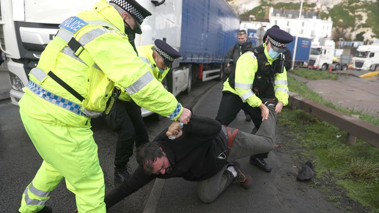 Police removed a man lying on the road in front of a lorry