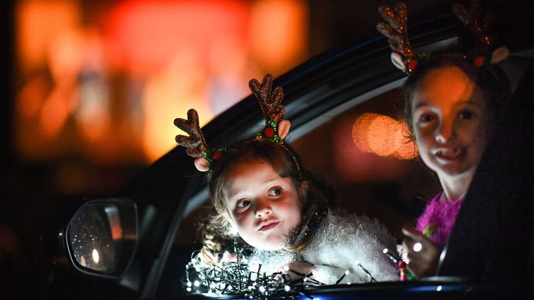 PERTH, SCOTLAND - DECEMBER 10: Two young girls look out of the car window as pupils, parents and guardians attend the Kilgarston Girls School drive-in movie on December 10, 2020 in Perth, Scotland. The school is putting on a Covid Christmas Movie, involving all 260 pupils and 100 staff, recorded over two weeks and shown tonight during three performances. (Photo by Jeff J Mitchell/Getty Images)