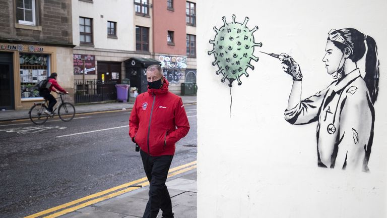 A member of the public walks past new artwork created by street artist The Rebel Bear in Edinburgh