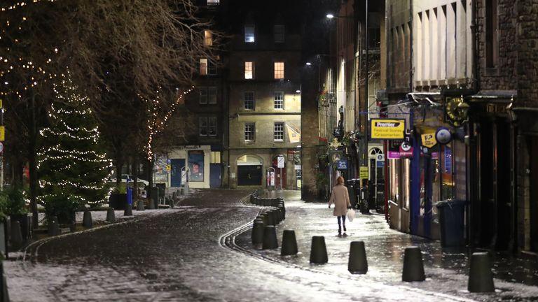 A person walks down a quiet Grassmarket in Edinburgh