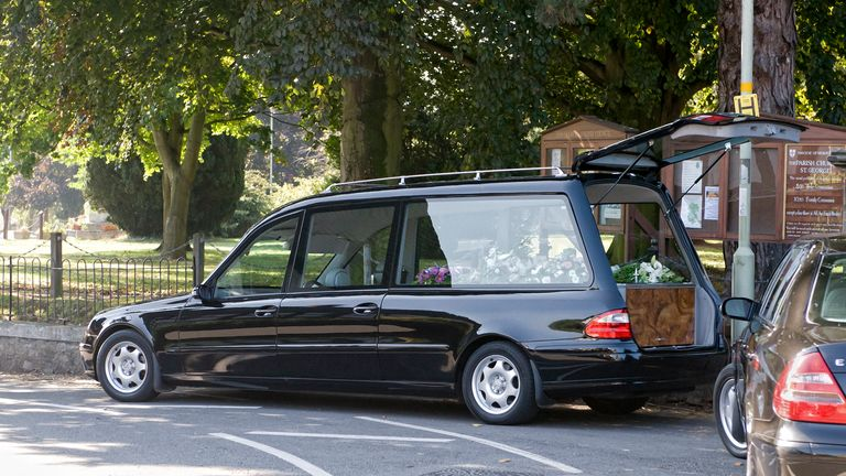 lack hearse outside Pontesbury church during a family funeral