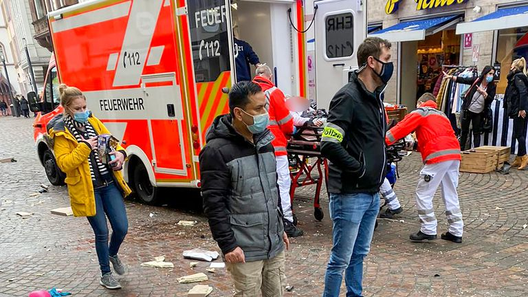 Police look on as rescuers push an injured person into an ambulance at the scene where a car drove into pedestrians in Trier, southwestern Germany, on December 1, 2020. - At least two people were killed and several injured when a car drove into a pedestrian zone in the southwestern German city of Trier on December 1, 2020, police said, adding that the driver had been arrested. (Photo by Sebastian SCHMITZ / various sources / AFP) (Photo by SEBASTIAN SCHMITZ/AFP via Getty Images)