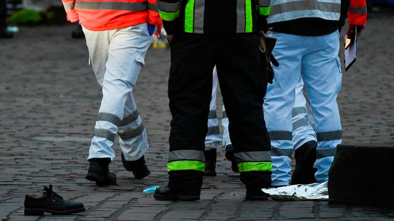 A shoe from a victim is seen on the ground next to emergency workers at the scene where a car drove into pedestrians in Trier, southwestern Germany, on December 1, 2020. - At least two people were killed and several injured when a car drove into a pedestrian zone in the southwestern German city of Trier on December 1, 2020, police said, adding that the driver had been arrested. (Photo by Jean-Christophe VERHAEGEN / AFP) (Photo by JEAN-CHRISTOPHE VERHAEGEN/AFP via Getty Images)