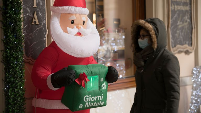 A woman wearing a face mask walks past the Christmas decorations in a shop in Turin, Italy