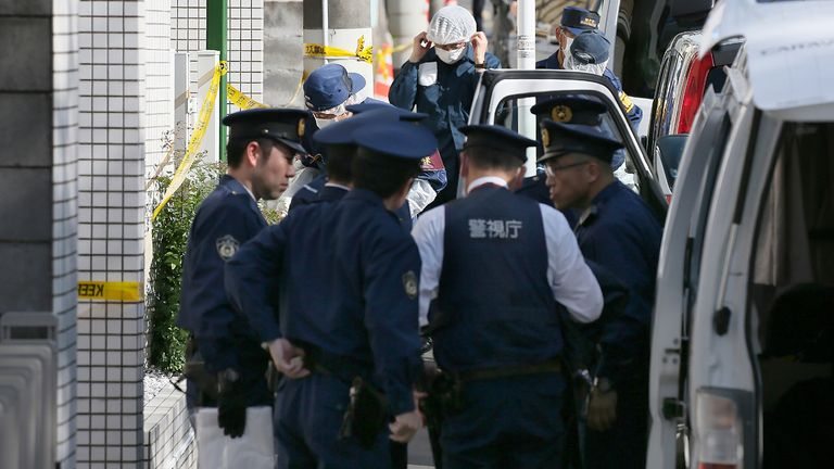 Policemen prepare for inspection in front of an apartment in Zama, Kanagawa prefecture, on November 2, 2017, where police found nine dismembered corpses. Takahiro Shiraishi, the Japanese man who has reportedly confessed to murdering and hacking up nine young people in his bathroom, was said to be a quiet schoolboy who would grow up to be a sex scout and suspected serial killer. / AFP PHOTO / JIJI PRESS / STR / Japan OUT (Photo credit should read STR/AFP via Getty Images)