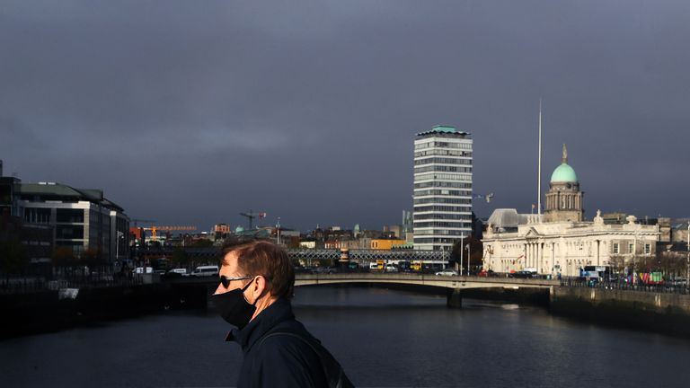 A man wearing a face mask crosses the Liffey in Dublin's city centre. Oct 2020