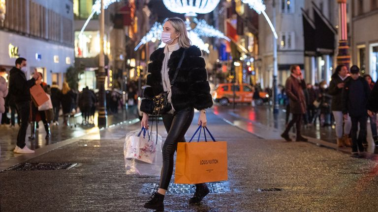 Shoppers pass Christmas light displays on New Bond Street in central London