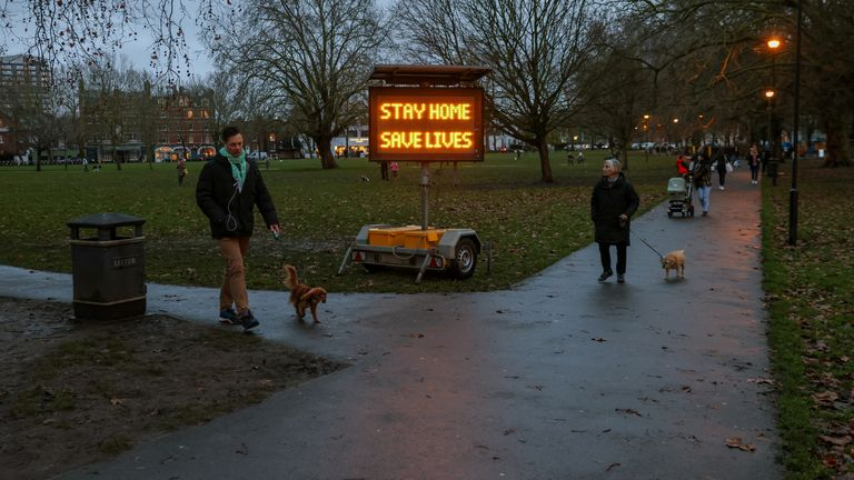 People walk past a newly placed sign on Eel Brook Common as EU countries impose a travel ban from the UK amid alarm about a rapidly spreading strain of coronavirus, in Fulham, London, Britain, December 21, 2020. REUTERS/Kevin Coombs