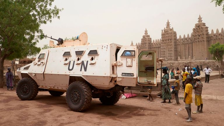 An armoured vehicle of the United Nations Multidimensional Integrated Stabilisation Mission in Mali (MINUSMA) patrols during the annual rendering of the Great Mosque of Djenne in central Mali, on April 28, 2019. - Several thousand residents of the historic central Malian city of Djenne, a UNESCO World Heritage site, took part in the annual rendering ceremony of the Grand Mosque, which will now be powered by solar electricity. The rendering of the building with banco (a mixture of soil and water,