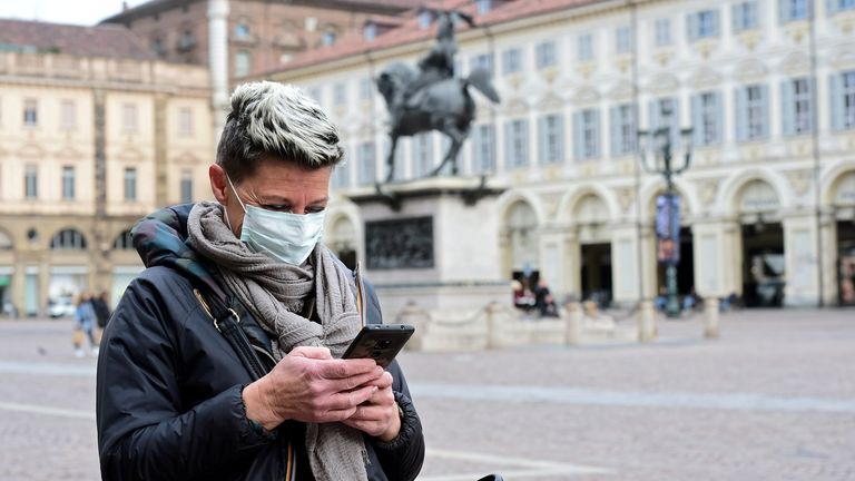 A woman wearing a protective mask uses her mobile phone, as a coronavirus outbreak continues to grow in northern Italy, in Turin, Italy, February 27, 2020
