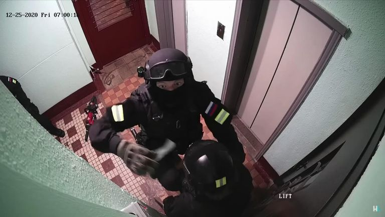 In this footage, men in police uniforms can be seen. One of the men uses tape to cover up the CCTV camera.