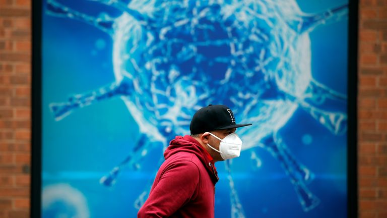 A man wearing a protective face mask walks past an illustration of a virus outside a regional science centre, as the city and surrounding areas face local restrictions in an effort to avoid a local lockdown being forced upon the region, amid the coronavirus disease (COVID-19) outbreak, in Oldham, Britain August 3, 2020